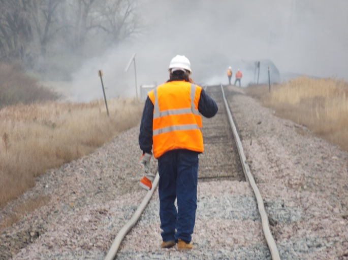 A BNSF maintenance worker stops to talk on his cell phone while inspecting the tracks just east of the accident site. Just ahead of him is the end of the stretch where the track has beeen raised