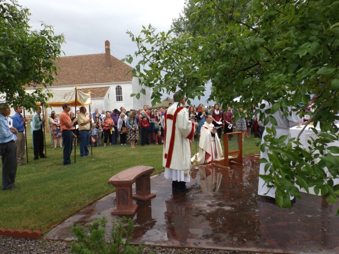 Father John Paul Gardner leads attendees in prayer at an outside altar.